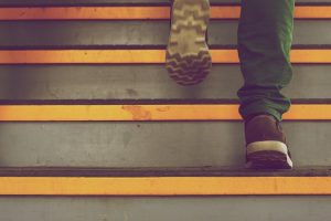 Ruskeakenkäinen henkilö kävelee rappusia ylöspäin.