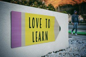 """Kivinen seinä kadulla, jossa lyijykynänmuotoinen posteri jossa teksti """"love to learn""""."""