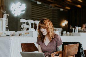 Punahiuksinen nainen istuu kahvilassa pöydän äärellä ja kirjoittaa tietokoneella hymyillen.