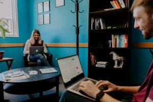 Mies ja nainen istuvat toimistossa eri puolella huonetta tietokoneet sylissään.