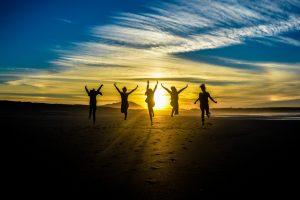 Viisi henkilöä hyppii hiekkarannalla auringonlaskussa. Taivas on sininen.