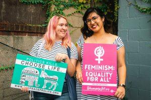 Kaksi naista hymyilee ja pitelee kylttejä, jotka ottavat kantaa tasa-arvoon.